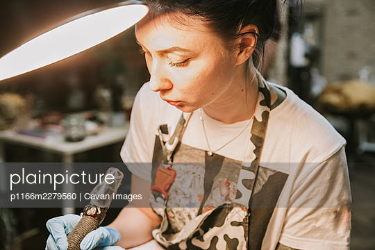 Portrait of a woman tattoo master showing a process of creation tattoo on a hand under the lamp light. - p1166m2279560 by Cavan Images