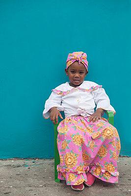 Dunkelhäutiges Mädchen sitzt vor Wand - p045m1590207 von Jasmin Sander