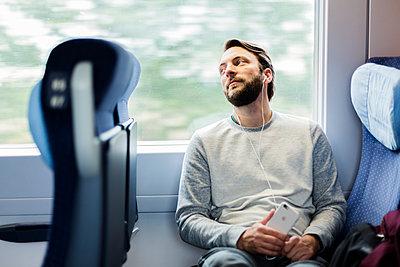 Mann hört Musik im Zug - p1114m1159730 von Carina Wendland