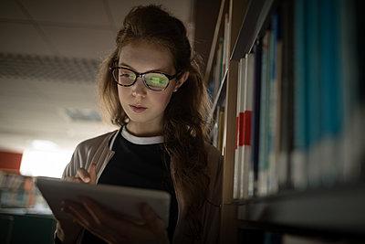 Woman using digital tablet in library room - p1315m1514617 by Wavebreak