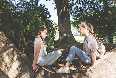 Two girls sitting on a tree trunk - p1402m2212023 by Jerome Paressant