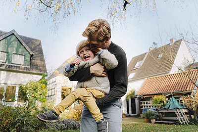 Happy father playing with son in garden - p300m2166648 by Kniel Synnatzschke