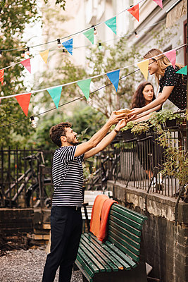 Young woman giving food to smiling male friend from balcony during garden party - p426m2046208 by Maskot