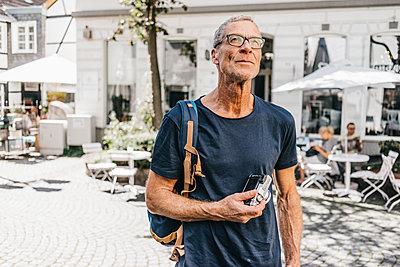 Reifer Mann mit Fotokamera in der Stadt - p586m1171821 von Kniel Synnatzschke