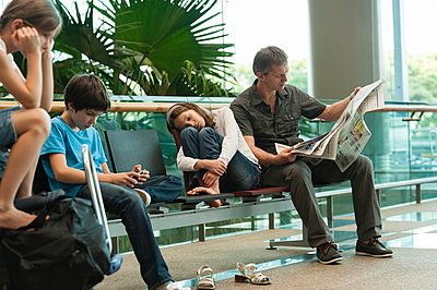 Family waiting in airport terminal - p623m659317f by Thierry Foulon
