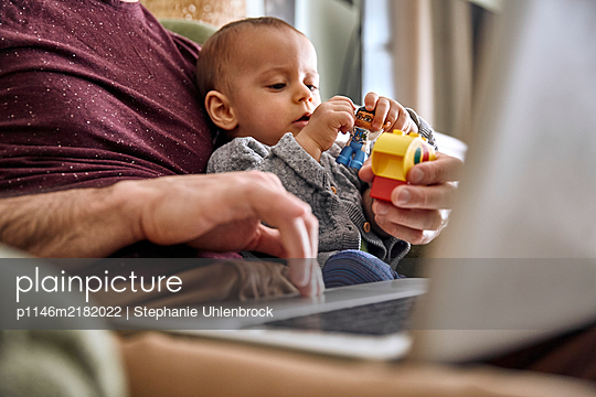 Father with laptop and baby boy, Stay at home due to Covid-19 - p1146m2182022 by Stephanie Uhlenbrock