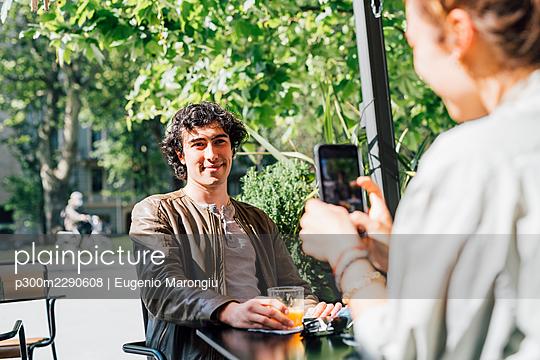Girlfriend photographing boyfriend through mobile phone at sidewalk cafe - p300m2290608 by Eugenio Marongiu