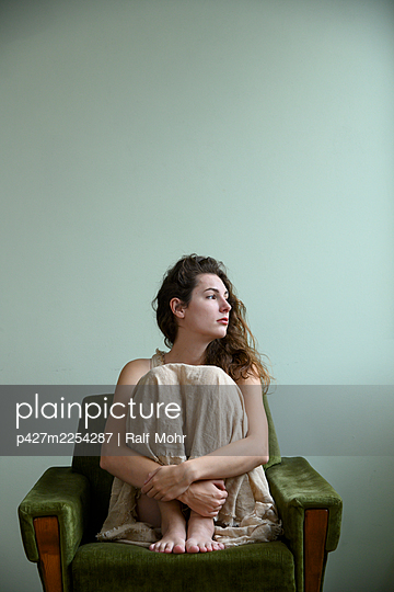 Young woman sitting on armchair - p427m2254287 by Ralf Mohr