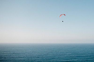 Person paragliding over sea - p1166m1533871 by Cavan Social
