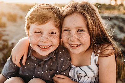 Portrait of young redheaded freckled siblings smiling during sunset - p1166m2136570 by Cavan Images