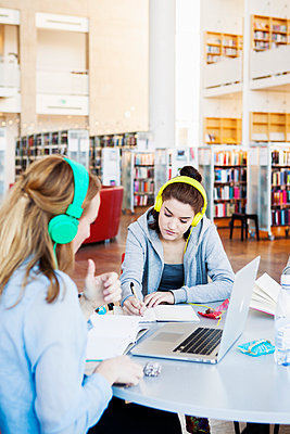 Woman writing notes while wearing headphones connected to laptop in library - p1185m1027604f by Astrakan