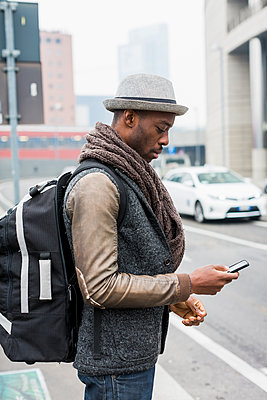 Stylish man with backpack standing beside road looking at cell phone - p300m1416921 by Mauro Grigollo