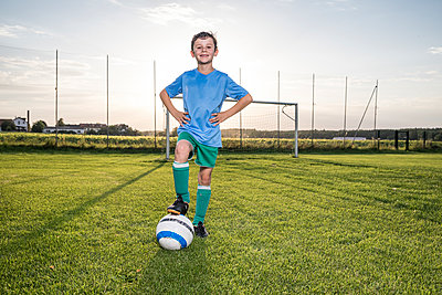 Portrait of confident young football player with ball on football ground - p300m1581517 by Fotoagentur WESTEND61