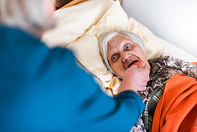 Woman taking care of old woman lying in bed - p300m1587924 by Daniel Ingold