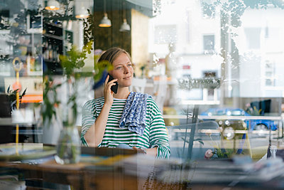 Smiling young woman on cell phone in a cafe - p300m2059111 von Kniel Synnatzschke