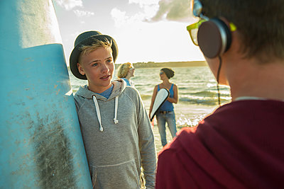 Two teenage boys communicationg on the beach - p300m965537f by Uwe Umstätter