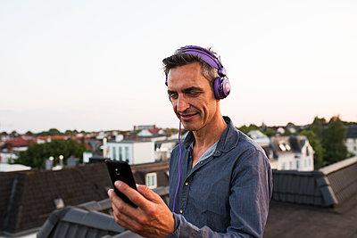 Man wearing headphones - p341m2008662 by Mikesch