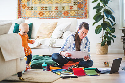 Fashion designer examining papers while daughter playing in living room - p426m2117006 by Maskot