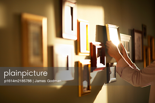 Woman putting pictures on the wall - p1614m2185788 by James Godman