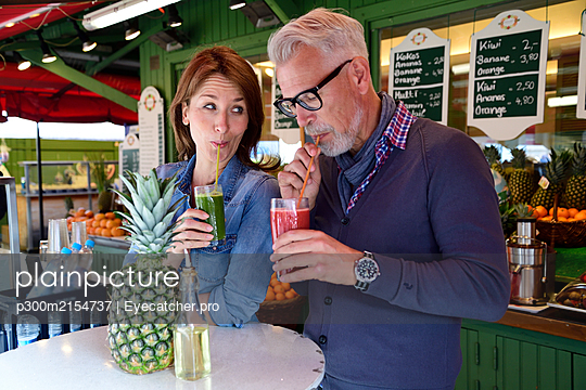 Mature couple drinking a healthy juice at a market stall - p300m2154737 by Eyecatcher.pro