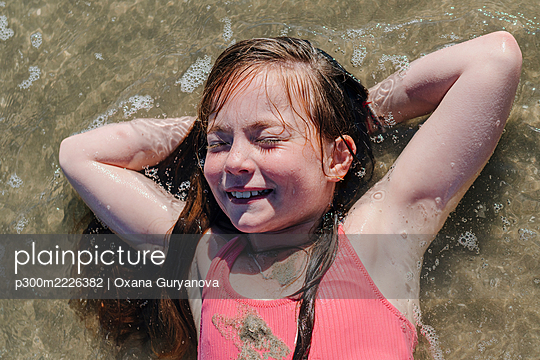 Girl lying on back with hands behind head in water during sunny day - p300m2226382 by Oxana Guryanova