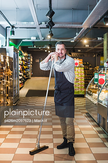 Full length portrait of smiling mature entrepreneur holding broom while standing in store - p426m2097623 by Maskot