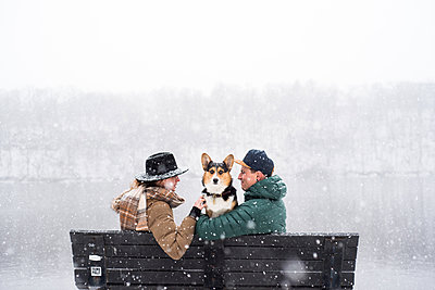 Couple with their dog locking eyes on a bench during a heavy snowfall - p1166m2095375 by Cavan Images