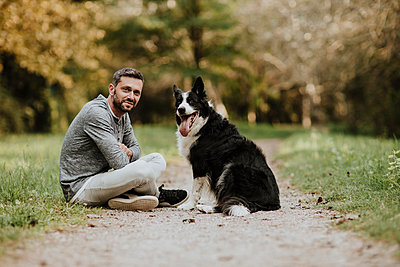 Smiling man and dog sitting on footpath at public park - p300m2226264 by Gala Martínez López