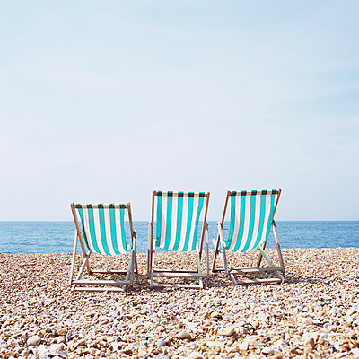 Three deckchairs on a shingle beach - p92410156f by Image Source