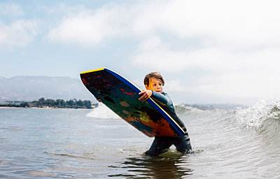 Portrait of young boy wearing wet suit in ocean, holding bodyboard, waiting for wave, Santa Barbara, California, USA. - p924m2208562 by JFCreatives