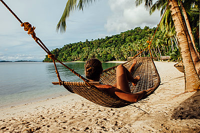 Young woman resting in hammock at beach - p1166m1530137 by Cavan Images