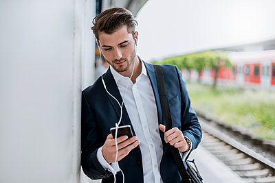 Businessman at the station with earbuds and cell phone - p300m2005645 by Daniel Ingold