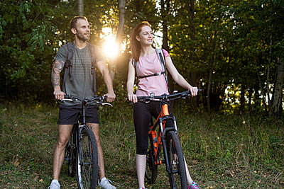Smiling young couple standing with bicycles in forest - p623m2294857 by Frederic Cirou