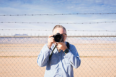 Photographer in front of barbed wire fence in desert taking photograph, California, USA - p924m1422807 by Raphye Alexius