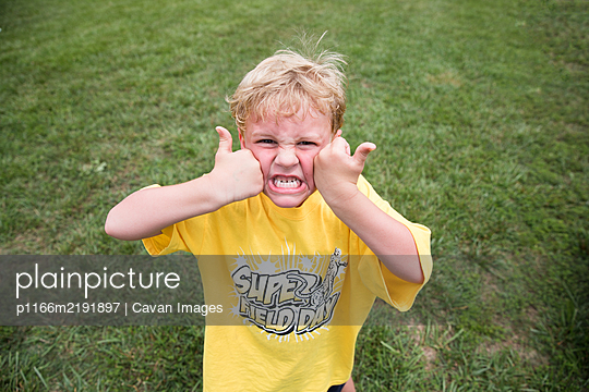 Silly Blonde Boy Squishes Face With Two Thumbs Up at School Field Day - p1166m2191897 by Cavan Images
