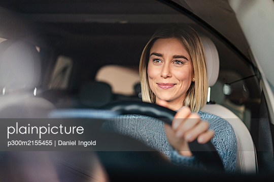 Portrait of smiling young woman driving a car - p300m2155455 by Daniel Ingold