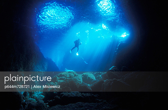 A diver hovers inside the archway as late afternoon sun streams in, Blue Maomao Arch; Poor Knights Islands, New Zealand - p644m728721 by Alex Misiewicz
