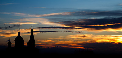 Church in background against sunset with clouds - p1166m2071998 by Cavan Images