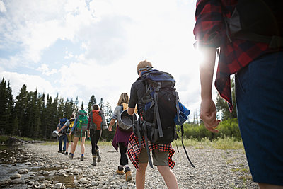 Teenage outdoor school students hiking along stream in woods - p1192m1490940 by Hero Images