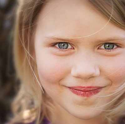 Portrait of young girl looking at camera mischievously, close-up  - p1531m2264172 by Jens Lucking