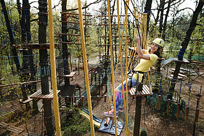 Young woman wearing yellow t-shirt and helmet in a rope course - p300m2102866 by Ekaterina Yakunina