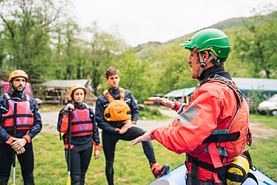 Instructor talking to group of friends at a rafting class - p300m2114107 by Francesco Buttitta