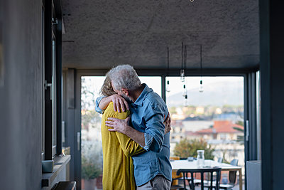 Affectionate senior couple embracing while standing at home - p300m2265908 by Emma Innocenti