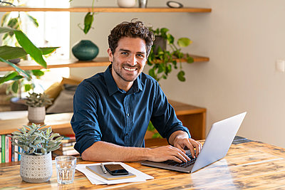 Happy male freelancer working from home through laptop - p300m2277448 by Steve Brookland