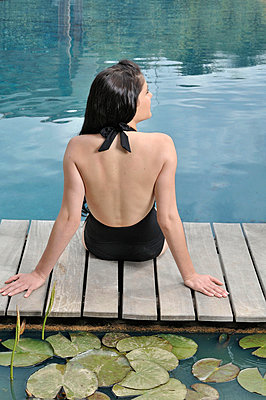 Woman sitting by the swimming pool - p4293050f by Luc Beziat