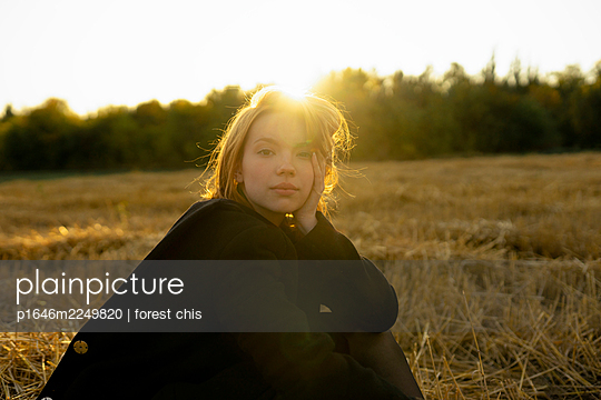 Young woman in stubble field in the evening sun - p1646m2249820 by Slava Chistyakov