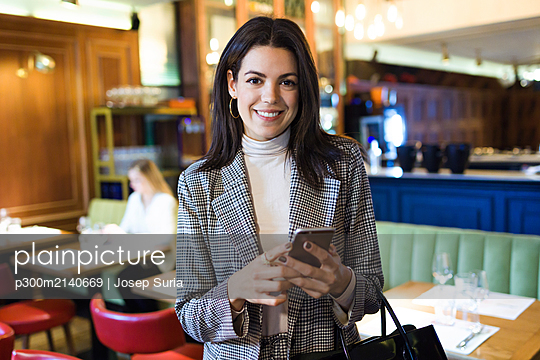 Portrait of smiling businesswoman holding cell phone in a restaurant - p300m2140669 by Josep Suria