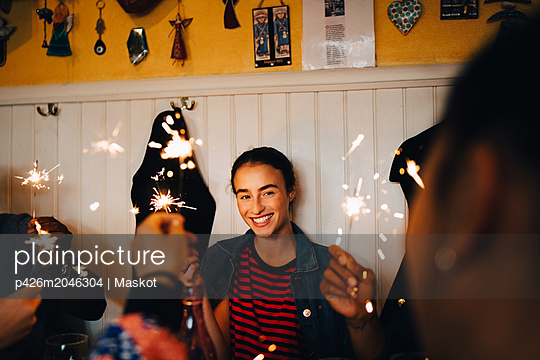 Smiling young multi-ethnic friends holding burning sparklers while enjoying in restaurant during dinner party - p426m2046304 by Maskot