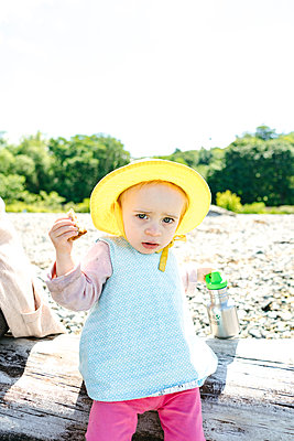 Portrait of a toddler in a sun hat eating lunch at the beach - p1166m2289977 by Cavan Images