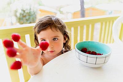 Cute little girl with raspberries on her fingertips - p300m2131895 by Gemma Ferrando